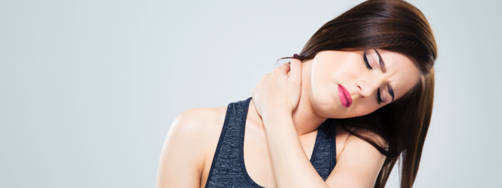 Fitness young woman with neck pain over gray background, Credit: Stock Photography