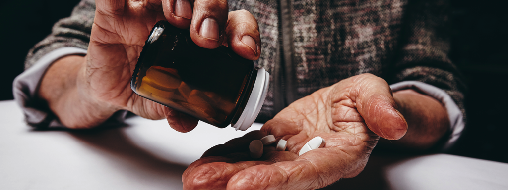 Senior female's hands pouring pills on her palm while sitting at a table., Credit: Stock Photography