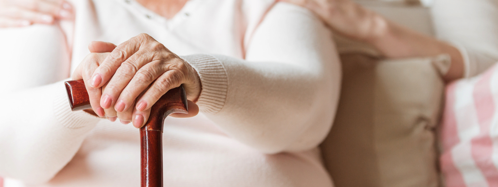 Close-up of an elderly woman's hands on a cane. Blurred background. Credit: Stock Photography