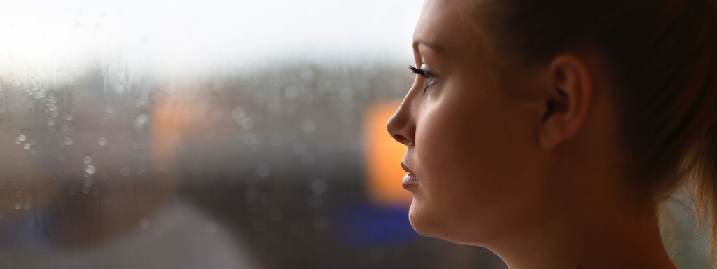 Woman Looking Out Window Concerned, Credit: Stock Photography