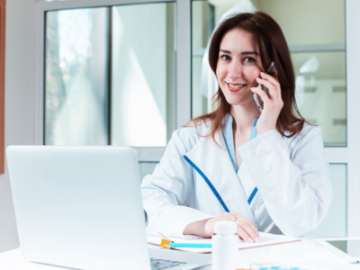 Female Doctor Smiling on Phone, Credit: Stock Photography