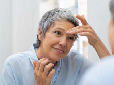 Senior Woman Touching Face, Credit: Stock Photography